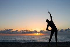 Het menselijke silhouet die ochtend doen werkt op het strand uit bij zonsopgang royalty-vrije stock foto