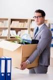 Het mensen bewegende bureau met doos en zijn bezittingen stock afbeelding