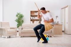 Het mensen schoonmakende huis met bezem stock fotografie