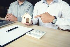 Het mensenteken een huisverzekeringspolis inzake huisleningen, Agent houdt lening Stock Fotografie