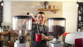 Het mensenwerk als Barista in een koffiewinkel, giet hij melk in een Kop van koffie stock video
