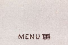 Het menuwoord met pictogram dat van geroosterde koffiebonen hierboven wordt gemaakt op linnentextuur, schot van, richtte bodemcen stock afbeelding