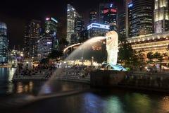 Het Merlion-standbeeld voor de horizon van Singapore bij nacht Royalty-vrije Stock Foto