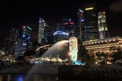 Het Merlion-standbeeld voor de horizon van Singapore bij nacht Stock Afbeelding