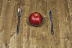 Het mes, de vork en de appel liggen op een houten oppervlakte Stock Afbeeldingen