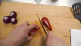 Het mes snijdt rode groene paprika op houten scherpe raad klem Scherpe kern in paprika op houten scherpe raad verwijder stock video