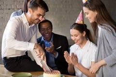 Het mes van de feestvarkenholding sneed de cake door collega's wordt voorgesteld die royalty-vrije stock foto