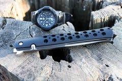 Het mes is vouw en horloge Houten stomp Stock Fotografie