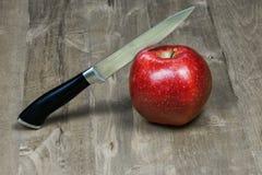 Het mes wordt gesneden door een appel liggend op een houten oppervlakte Royalty-vrije Stock Fotografie