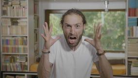 Het met afschuw vervulde jonge mens het gillen reageren van iets enge het uitdrukken verschrikking en schok - stock footage