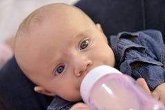 Het met de fles grootbrengen van halfjaarlijks babymeisje Stock Foto's