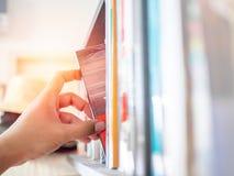 Het met de hand plukken van een boek stock foto's