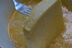 Het met een laag bedekken van de kaasplak in gezwaaide eieren Stock Afbeelding