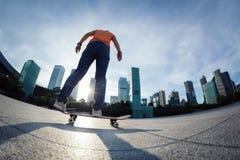 Het met een skateboard rijden bij zonsopgangstad stock afbeelding