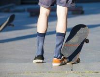 Het met een skateboard rijden - detail van skateboard en benen Stock Afbeeldingen
