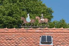 Het metaal figuur twee ruiters, de mens en vrouw op het dak van een landgoed Stock Foto