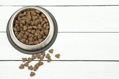 Het metaal om het voeden van kom met donker bruin hart gevormd huisdier verbrokkelt royalty-vrije stock afbeelding