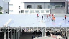 Het metaal van het arbeidersdakwerk voor het dak op een groot commercieel gebouw bij Petchkasem-weg Omnoi, Krathum Baen, Samut Sa stock video