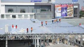 Het metaal van het arbeidersdakwerk voor het dak op een groot commercieel gebouw bij Petchkasem-weg Omnoi, Krathum Baen, Samut Sa stock videobeelden