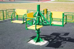Het metaal van carrouselkinderen groen op de Speelplaats met met rubber bekleede deklaag royalty-vrije stock foto