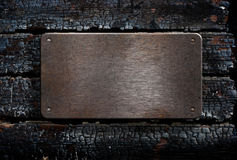 Het metaalplaat van Grunge over gebrande houten achtergrond Royalty-vrije Stock Afbeeldingen
