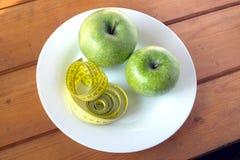 Het meten van band en rijpe groene appelen op plaat Stock Afbeeldingen