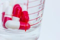 Het meten van glas met capsules royalty-vrije stock foto