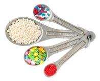 Het meten van lepels met verschillende soorten koekje bestrooit isolat royalty-vrije stock afbeeldingen
