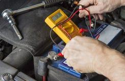 Het meten van voltage op autobatterij Veranderings zwakke batterij royalty-vrije stock afbeeldingen