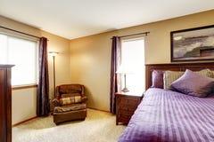 Het meubilair van de luxeslaapkamer met helder purper beddegoed Stock Afbeeldingen