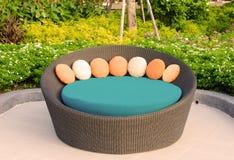 Het meubilair van de rotanleunstoel in tuin Stock Foto