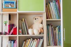 Het meubilair van kinderen met boekenrekken, boeken en teddybeer stock afbeeldingen