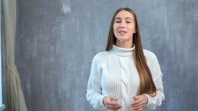 Het middel schoot portret van het mooie Europese sprekersvrouw spreken bij studio grijze achtergrond stock videobeelden