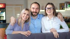 Het middelgrote close-up schoot groep jonge vrienden die en samen het stellen voor foto glimlachen koesteren stock footage