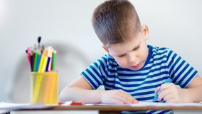 Het middelgrote ijverige close-up concentreerde weinig de tekeningsbeeld van de kindjongen gebruikend blauwe teller stock footage