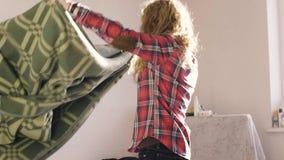 Het middelgrote schot van jonge vrouw behandelt de bank met een deken in de ochtend bij het plattelandshuisje stock footage