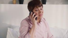 Het midden oude vrouw cellulair gebruiken thuis stock video