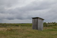 In het midden van de weidetribunes een rustiek openbaar toilet dat van houten planken wordt gemaakt royalty-vrije stock fotografie