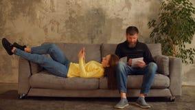 Het Millennial paar ontspannen op bank in zolderflat stock video