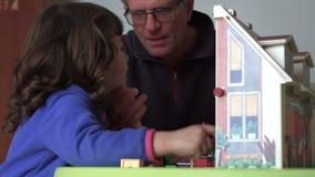 Het Millennial spontane kind en papa spelen met poppenhuis SF stock videobeelden