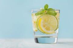 Het mineraal goot water met kalk, citroenen, ijs en muntbladeren op blauwe achtergrond, eigengemaakt detoxsodawater Royalty-vrije Stock Afbeelding