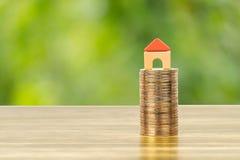 Het mini modelhuis op muntstukken stapelt concept voor hypotheek, financiën, en besparing stock afbeeldingen