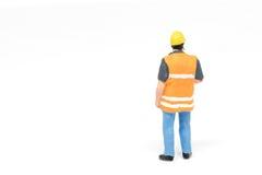 Het miniatuurconcept van de de veiligheidsbouw van de mensenarbeider op witte bac Royalty-vrije Stock Foto