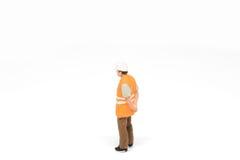 Het miniatuurconcept van de de veiligheidsbouw van de mensenarbeider op witte bac Royalty-vrije Stock Fotografie