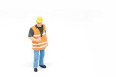 Het miniatuurconcept van de de veiligheidsbouw van de mensenarbeider op witte bac Royalty-vrije Stock Afbeeldingen