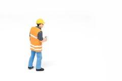 Het miniatuurconcept van de de veiligheidsbouw van de mensenarbeider op witte bac Stock Foto