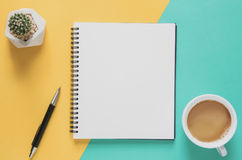 Het minimale concept van de bureauwerkplaats Leeg notitieboekje met kop van koffie, cactus, potlood op gele en blauwe achtergrond