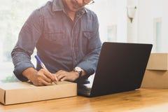 Het MKB-het Bedrijfsmens schrijven adres op pakket met labtop op de lijst royalty-vrije stock afbeeldingen