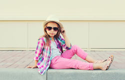 Het model die van het maniermeisje een roze geruite overhemd, een hoed en zonnebril dragen Stock Afbeelding