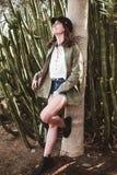 Het model lachen met zwart GLB die op de boomstam van een boom dichtbij cactus rusten stock foto
